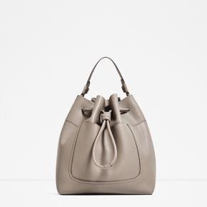 ZARA faux-læder taske i pæn grå, helt ny med mærke stadig på. Den har en god hverdag str., dog ikke stor nok til stor computer. Der er både hank og lang rem, så man kan have den over skulderen eller crossover også. Plus, har den en lom foran, hvor man nemt kan smide sine små ting i. Har også en i sort.   BYD! :-)