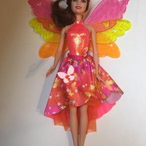 Barbie fe med vinger, ved tryk på ryggen slåes vingerne ud. Den er aldrig leget med, bare stået i et skab.