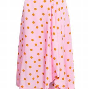 Smuk nederdel i pink/Rosa med orange prikker. Asymmetriske sømme forneden og a-snit.