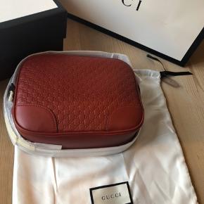 Skøn, rød Gucci logo taske i lammeskind. Jeg har lavet et impulskøb af to tasker denne sommer.  Jeg har både æske, pose og dustbag fra butikken.  Respekter venligst at jeg ikke bytter og køber betaler porto samt gebyr ved tspay.  Mål: 25 cm lang x 19cm høj x 7 cm dyb.