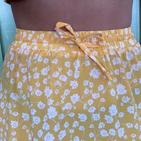 Fin gul og hvid blomstret nederdel med snørre i taljen så man kan stramme som man ønsker. Går til lige under knæene. Den passer en størrelse xs/s/m.