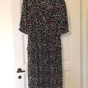 Fin vintage kjole med grafisk mønster  Plisse skørt med extra lille skød - meget klædeligt snit - falder flot  Mid-lenght  Den mangler str men jeg vil sige den er en str 40/42 - m/l  Syntetisk materiale men af god kvalitet som ikke klæber og bliver elektrisk