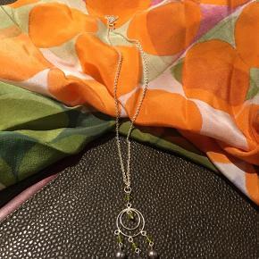 Smuk halskæde med forskellige sten. Lysegrønne og metallic lyslilla.  Aldrig brugt.  Kommer i original smykkepose.
