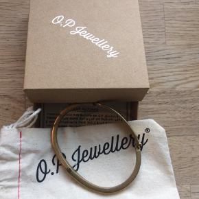 Armbånd fra svenske O.P. Jewellery  De har indgraveret to pile.  Original æske og pose følger med.  Det er messing og str. L.