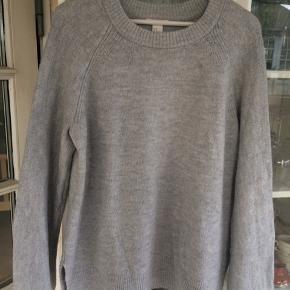 Dejlig sweater med slids forneden i lysegråt, meleret strik.