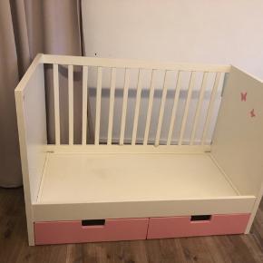 Sælger en stuvia juniorseng med lyserøde skuffer. Den populære seng med de gamle skuffefronter, er nu til salg.  Bunden kan hæves så baby kan sove trygt i den også.  Brugt af 1 barn. Rigtig god stand. Ny 1500kr   Denne seng sælges med madras og sengehest til 800kr  Sommerfuglene er lige til at pille af, men måske en lille pige skal have sengen, og vil elske dem lige så meget som min gjorde. Hvis sengen er til en dreng så kan sommerfuglene som sagt pilles af.  Begge tremmesider medfølger også.