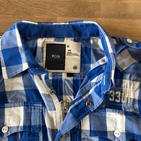 Skjorte med lynlås og knapper uden over. Np. 800kr