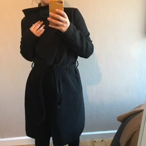 Sort frakke med bindebånd i livet, og store rummelige lommer.  Bytter ikke. Sendes via appen eller afhentes på adressen