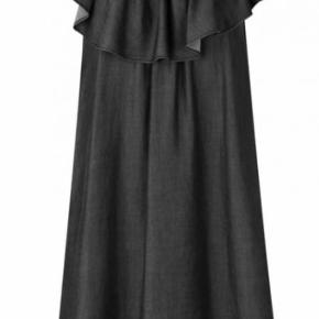 Fin knælang kjole med flæsekant (kan bruges off-shoulder) og lommer i siderne. Stof: 100% cupro.