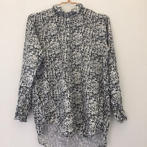Hvid med sort og grå/blå mønster.