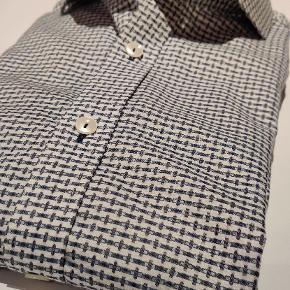 Langærmet skjorte fra Matinique. Hvid med småt blåt/gråt/hvidt mønster.