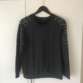 Fed sweater med spikes og nitter på ærmerne og distressed rund krave.  Materialer: 66% bomuld, 34% polyester.