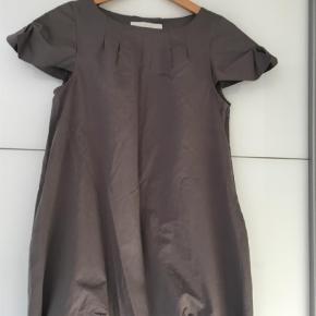 Varetype: Midi Farve: Grå  Super flot kjole, med lommer i siden og flotte detaljer ved ærmer