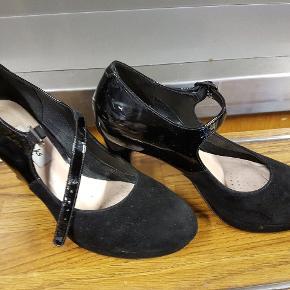 Båndet der går over den ene sko er lidt slidt (se billede) ellers er der minimalt slid.