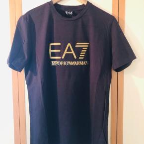 Frisk, behagelig sort T-shirt fra Armani med stort log for i guld sælges da den aldrig bliver brugt længe. T-shirten er fremstillet i det behagelige streg(?) stof så den sidder tæt ind på kroppen. Fremstår som ny, uden huller, pletter el anden slitage.  Som det kan ses på det ene billede er etiketten med str osv klippet af da den var irriterende når man bar T-shirten. Men str er som de andre to der også er annonce på XL. Alle tre er købt hos Armani på en ferie i Italien.  Giv et fair bud