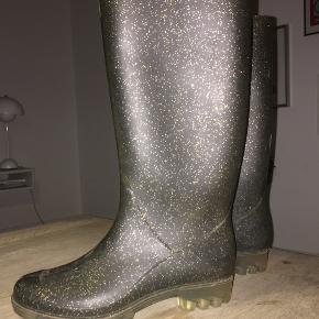 De lækreste gummistøvler i grålig (mørk grå) med glimmer. Sålen er gennemsigtig. De går til den øvre læg ( under knæ).