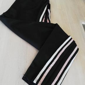Med lyserød og hvid stribe langs buksebenene.