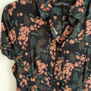 Gulvlang skjorte-kjole. Knapper ned til knæene. Korte ærmer. Sort med lyserøde blomster og grønne blade. Den er smal i taljen.  Ingen fejl eller mangler. Stoffet er blod tynd bomuld. Fra ZARA Premium Denim Collection.