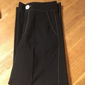 Bukser med vide og hvid kontrastsyning. Har en stor hvid knapNp: 300 kr