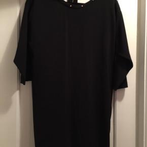 Sort kjole med nitter rundt i halsen og lidt åben på ryggen, kun brugt få gange.