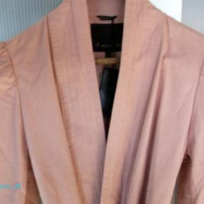 Varetype: **NY** Flot Blazer Farve: gl rosa Oprindelig købspris: 4250 kr.  Denne flotte blazer må videre, jakken er aldrig kommet i brug og derfor helt ny, den ville være lige til en kølig sommeraften.  Super lækker jakke i en frisk fin farve.med fine detaljer og bindebånd. Stýle WLR143 - farve 797.   Skal jakken sendes udenfor dk, skal portoen aftales med sælger.   Materiale er : 100% Cotton.   CA mål er: Længden 63 cm  Brystmål 2 x 56 cm   Min mp idé er omkring 1800 kr..     ¤¤¤ BYTTER IKKE ¤¤¤