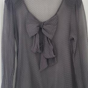 Scarlett Roos. Fransk tøjdesigner  I transparent grå silke. Med stor sløjfe effekt foran. Skulderpuder. Bindebånd ved ærmer. Str er mærket: 2.  = M/L