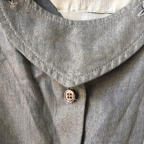 """Helt speciel skjorte fra Max Maras S-linje sælges, næsten som ny.  Farven er grålig med meget diskret guldglimmer. Mange detaljer, fx lille """"forstykke"""" der kan knappes af, stofdetalje ved brystet. Skjorten kan bruges med/uden tyndt bæltesnor, der medfølger.   Sælges for 125 kroner plus Porto."""
