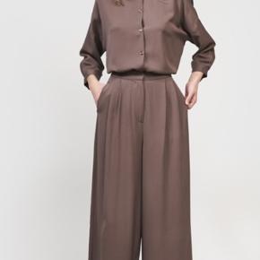 Meget fine silkebukser i en flot fin brun farve , bukserne er aldrig brugt  Og har tabs på. Bukserne har lenning med delvis elastik bag.Relevant bud ønskes