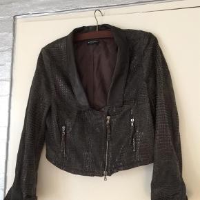 Brand: Blacky Dress, Berlin Varetype: Skingagtig flot materiale  Farve: Brun Oprindelig købspris: 1800 kr.  Kort, meget spændende jakke med fin skindagtig krave og lynlås. Lys og mørk brun , meget flot materiale .  63 procent polyester, 39 procent vinyl og 8 procent polyuretan. Flot til et par jeans. Har været meget dyr. GIV ET BUD