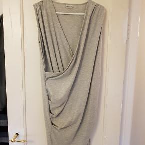 Helt ny grå kort slå-om/draperede kjole (kan også bruges som lang top). Superflot pasform, og desuden super-velegnede til amning selvom det ikke er ammekjoler. 92% bomuld/8% elestan.  NB! Billedet af den i sort er kun for at vise pasform  Aldrig brugt, da den er for stor.  Mål Længde: 92cm