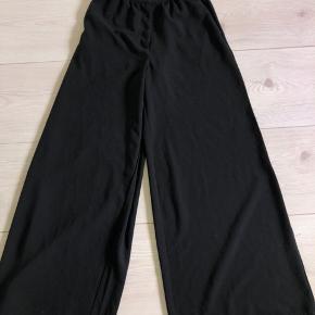 Plisserede vide bukser fra Y.A.S. Bukserne har meget brede ben, med en smal talje omkreds.  Brugt 1 gang, har ingen tegn på slid og fremstår derfor som nye.   BYD