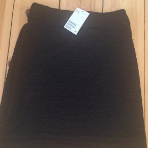 Sort H&M nederdel med stretch så den giver sig. Den sidder stramt.