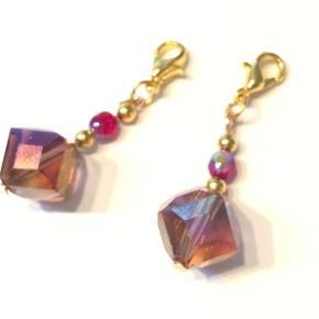Charms fra Walina  Vedhæng til halskæde tasker punge - Prisen er pr stk  Brug den som pynt til: - dine lynlåse til dit penalhus, taske eller pung - din nøglering - din eksisterende halskæde  Den består af en lilla facet-perle med machende perler på forgyldt lås. . I alt er den 3,5 cm lang.  Jeg kan handle med mobilpay: Jeg sender gerne med post nord til din postkasse (+10 kr 5 dages leveringstid eller 29 kr 1 dags leveringstid), hvis du ikke kigger forbi og henter den. Jeg kan handle via Tradono med DAO pakkepost (+32 kr), hvor du afhenter pakken ved ønsket DAO udleveringssted  Mvh Lise