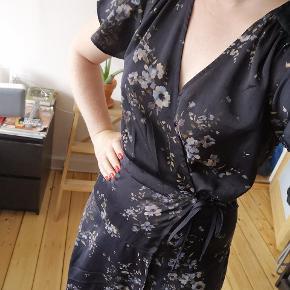 Fin slå-om kjole med blomstermønster. Har knap i siden, så kjolens snørre og slå-om effekt bliver hvor den skal ved bevægelse.