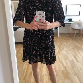 Helt ny kjole fra Ganni sælges. Kjolen har det smukkeste, sommerlige blomsterprint, og passer perfekt til både hverdag og fest. Selve kjolen er i to tynde lag, mens ærmerne kun har et, hvilket skaber et super fint og feminint look. Desuden er der en lille flæsekant på bunden af kjolen og på bunden af ærmerne. Nypris var 999,- og kvittering haves, og sælges fordi de 7 dages refunderingsret (med penge udbetalt) er opløbet. Køber betaler fragt, hvis varen skal sendes.