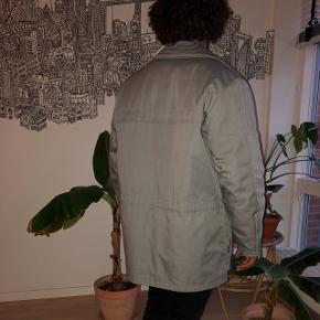 Sjælden vintage jakke fra 70erne i perfekt/ubrugt stand af det danske mærke mammut. Kan fint bruges som vinterjakke. Grå farve med blåt for. Der er en snor, som km spændes ind i taljen, hvis man ønsker det. Mange gode lommer til ting og sager.  Størrelsen er en M/L  Kom med et bud.