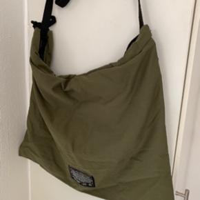 Har ET xtra til salg! Army/khaki/oliven farvet let blød unisex multi Tote bag med flere muligheder i forhold til remme og indsnøringsbånd. Der er UO logo foran samt to lommer indeni. Mål: længde ca 38 cm og bredde ca 45-46 cm. De korte hanke måler ca 60 cm og den lange ca 115 cm. Materiale er polyamid/nylon. Sælges for under 1/2 pris pp (Minimum 150 inkl med DAO & MobilePay)