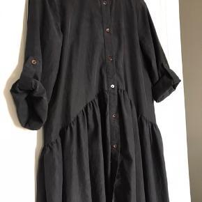 Fineste skjorte / skjortekjole. Den er ikke helt sort men gråsort. Har klippet vaske mærket ud men den er af cupro.  Ærmerne kan hægtes som på billederne med knap eller rulles ned. De er ikke helt lange.  Brugt men i fin stand.  Køber betaler Porto.