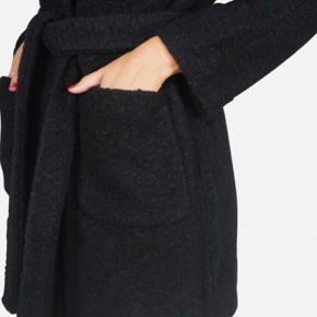 Fin klassisk ikke fra Ganni.   Slå om-frakke i strukturmønstret bouclé-uld med bælte og store, påsyede lommer.  Jakkens ydre er rigtig fin. Desværre er der et lille hul i foret inden i ærmet (i syningen, så det kan syes), og ses i sagens natur ikke, når den er på, men derfor prisen :)  Se billede 3.