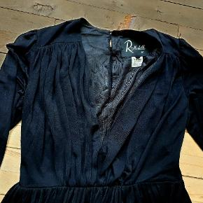 Vintage kjole. Den måler 104 om brystet, 84 i taljen som er fast. Underkjolen måler 134 i omkreds og yderstoffet som er elastisk og lidt gennemsigtigt måler over 200 cm i omkreds. Den er 118 lang. Den har lynlås i siden og ærmerne er gennemsigtige.