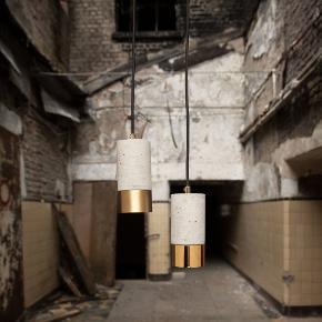 Lækker og rå lampe, der kombinerer det industrielle og tidløse udseende af beton med den feminine elegance af messing, kobber eller aluminium (Fås således i alle 3 modeller)  En unik og smuk materiale kontrast fra beton til den 2 mm tykke ring af messing.  Lampen fås ligeledes i lys eller mørk beton.  I dag er materialernes ægthed i forgrunden, så naturlige egenskaber ikke betragtes som mangler, men bevidst fremhæves. Vi agter at have små luftlommer i betonen. Selv små revner beskadiger ikke betonens stabilitet og bidrager til lampens karakter.  Denne lampe leveres med en GU10 fatning ? så selve lyskilden holder sig inde i lampen.  Kabellængde: 1,9 m  Højde: 17 cm  Diameter: 8 cm  Vægt: 1,2 kg pr. lampe  Maks. belastning: 230 v/ 50 W  Dæmpbar: Muligt  Pris pr. lampe er DKK 1.495. Køb et sæt af 3 lamper til DKK 3.495.   Der er tale om helt nye lamper - se mere på www.designhome.dk eller skriv gerne til os.