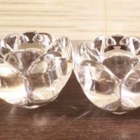 2 x Lotusstager stor, 9cm fra Holmagaard glasværksted Royal Copenhagen - Torben Jørgensens har designet sine Lotusstager fra 1993 som en hyldest til den magi, der kun kan skabes med levende lys. Glassets form og varierende tykkelse giver flammens mange udtryk smukke rammer at udspille sig i.  Lotusstagerne findes i tre størrelser, disse er 9cm og den største størrelse og er smukke både alene og i flok på bordet, i vindueskarmen – og på trappen som en velkomst til dine gæster.   Stagerne har været i brug men bliver afleveret rengjorte og stort set uden brugsspor.  NYPRIS 250kr Per stk  Sælges samlet til prisen  #30dayssellout