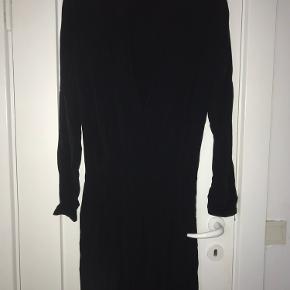 Kort, sort kjole fra Samsøe & Samsøe. Høj hals, lange ærmer og bar ryg samt elastik i taljen.   Lidt make-up på indersiden af halsen.   Sender ikke - alt kan hentes på Emdrup St. i København.