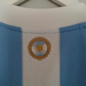 Lækker Argentina fodboldtrøje til herrer.  Nypris = 500 kr. Købt i sportmaster.  Brugt få gange. Fejler intet.  Super behagelig kvalitet ( clima cool )  Sendes med DAO.  MOBILEPAY foretrækkes.  PRSEN ER FAST. FORHANDLES IKKE.