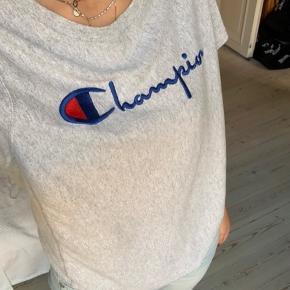 Lysegrå Champion t-shirt. Den har ikke tegn på slid, men den er blevet brugt og vasket et par gange. str. small. Kom med et bud.