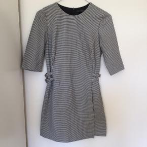 Hvid og sort ternet romper/jumpsuit fra Zara. Ligner en nederdel forfra, men er faktisk shorts. Tætsiddende og rar. Fine detaljer i siderne på taljen, med mulighed for at løsne/stramme. Den passes kun af en xsmall