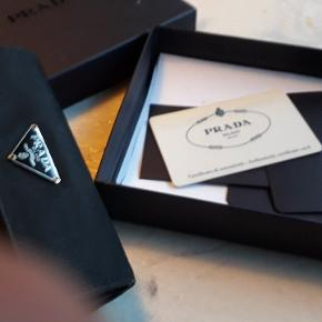 Prada pung købt i Milano  Der er original æske samt certifikat og ægtheds bevis med   Der er alm brugs slittage  men ingen fejl og mangler Sender med dao   mangler