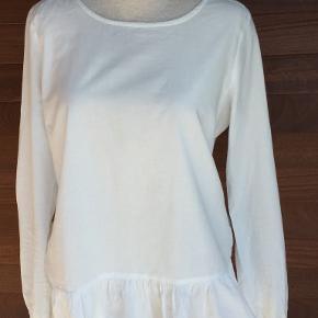 Flot hvid trøje med detalje forneden - se foto.  Portoen er 36 kr. som køber betaler.  Bytter ikke. Se også mine øvrige annoncer. Betaling via mobilepay og sender med DAO fra dag til dag. (10)