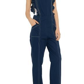 Ganni Phillips Cotton buksedragt med flæser og åben ryg. Brugt få gange, god stand.