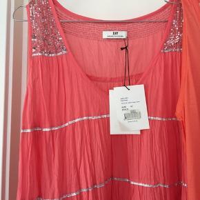 Superfin koralfarvet kjole med masser af vidde og creppet effekt. Dertil orange/koral stumpeleggings og lang tynd top. Superflot sammen . Alle dele med prismærke , ialt 1700 fra ny